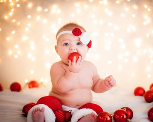Baby's first Christmas Photo Ideas - Adorable Baby eating an ornament